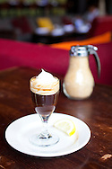 Busboys and Poets is a restaurant, bookstore, fair trade market and gathering place where people can discuss issues of social justice and peace. Busboys and Poets creates an environment where shared conversations over food and drink allow the progressive, artistic and literary communities to dialogue, educate and interact. Pictured here is the Café Medici which contains chocolate added to two shots of espresso, topped with whipped cream and served with a lemon wedge.