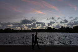 © Licensed to London News Pictures. 16/10/2017. London, UK. A couple walk by at sunset over the Round Pond in Kensington Gardens.  Dust brought by winds from Hurricane Ophelia caused the sun to appear a mysterious reddish orange colour against an orange sky. Photo credit : Stephen Chung/LNP