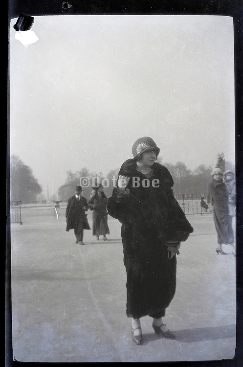 female person in fur coat walking in public park early 1900s Paris