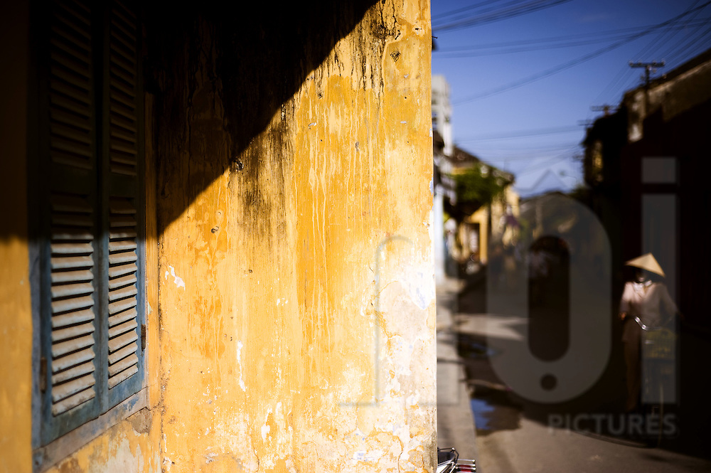 Yellow wall hit by the sun in Hoi An, Vietnam, Asia. A woman with her conical hat rides a bicycle in the background.