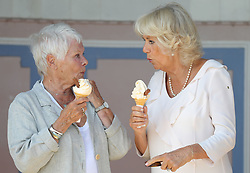 The Duchess of Cornwall enjoys an ice cream with Dame Judi Dench as she arrives at Queen Victoria's private beach, next to the monarch's holiday home in East Cowes on the Isle of Wight. Dame Judi, patron of the Friends of Osborne House, will show Camilla the newly restored Durbar Room, which was one of the locations for the film Victoria and Abdul in which she played Queen Victoria.