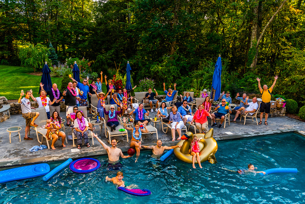 A gathering of family and friends by the backyard swimming pool at a home in Danbury, Connecticut USA.
