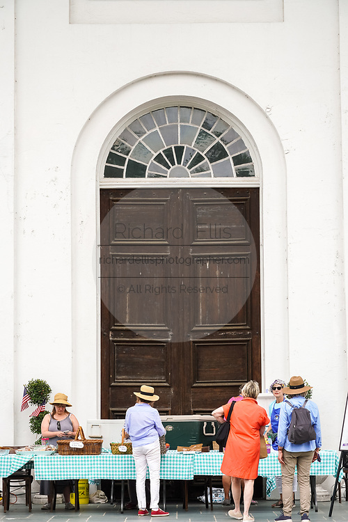 People enjoy an alfresco meal on the portico of the Second Presbyterian Church during a outdoor art show and food event on Wragg Square in the historic district May 29, 2021 in Charleston, South Carolina.