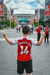 "© Licensed to London News Pictures. 01/08/2020. LONDON, UK. A young Arsenal wearing a shirt in support of Arsenal captain Pierre-Emerick Aubameyang poses outside Wembley Stadium two hours before the FA Cup Final between Arsenal and Chelsea.  Normally taking place in May, the competition had to be rescheduled due to the coronavirus pandemic.  No spectators or fans will be allowed in the stadium, it will be the first ""Fanless FA Cup Final"".  Photo credit: Stephen Chung/LNP"