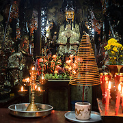 Candles and incense burn at a small shrine at the Jade Emperor Pagoda in the Da Kao district of Ho Chi Minh City, Vietnam. The Chinese temple was built in 1909 and contains elements of both Buddhist and Taoist religions.