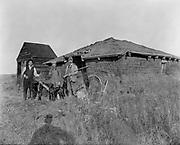 0608-136.  three hunters next to Nebraska sod house, probably a hunting cabin. about 1910.