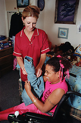 Care manager in residential care centre helping young woman with Cerebral Palsy to put her jacket on,