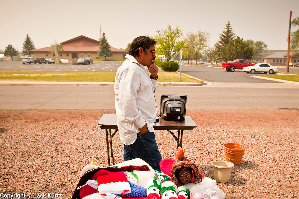 """03 JUNE 2011 - SPRINGERVILLE, AZ: Smoke fills the air while Jake Gomez (CQ) from Eager, looks at stuff for sale at a yard sale in Eager Friday. Gomez said he was concerned that the Wallow Fire might reach Eager. He said his home is surrounded by pinon juniper and cedar and they burn hot.  High winds and temperatures have continued to complicate firefighters' efforts to get the Wallow fire under control. The  mandatory evacuation order for Alpine was extended to Nutrioso, about 10 miles north of Alpine and early Friday morning fire was reported on the south side of Nutrioso. The fire grew to more than 106,000 acres early Friday with zero containment. A """"Type I"""" incident command team has been called in to manage the fire.  PHOTO BY JACK KURTZ"""