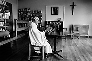 A monk reading a bible in the library at Sancta Maria Abbey at Nunraw, East Lothian, home since 1946 to the Order of Cistercians of the Strict Observance. Around 15 monks were resident at Nunraw in 1996, undertaking a mixture of daily tasks and strict religious observance. The present purpose-built building dates from 1969 when the monks moved from the nearby Nunraw house.