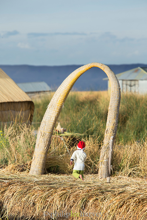 Boy with santa hat plays on the floating islands, Lake Titicaka, Puno, Peru, South America