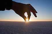 A hand dips down to pinch the sun as it sets over the natural salt flats on the shores of Laguna San Ignacio, Baja California Sur, Mexico.