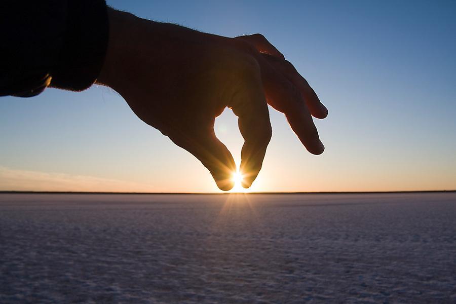 A hand dips down to pinch the sun as it sets over the natural salt flats on the shores of Laguna San Ignacio, Baja California Sur, Mexico.