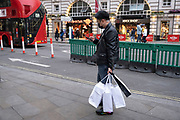 Man with his shopping bags as Londoners await the announcement of a second coronavirus lockdown it's business as usual in the West End with people out and about on what will be the last weekend before a month-long total lockdown in the UK on 30th October 2020 in London, United Kingdom. The three tier system in the UK has not worked sufficiently, to suppress the virus, and there have have been calls by politicians for a 'circuit breaker' complete lockdown to be announced to help the growing spread of the Covid-19.
