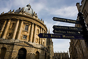 """From a low-viewpoint, we see the famous Oxford landmark, the Radcliffe Camera with a series of direction signs pointing to other famous Oxford locations on the tourist trail such as the nearby Bodleian Library the Sheldonian Theatre and the city University museum The round building is in afternoon sunshine without people or interferring features. The Radcliffe Camera (colloquially, """"Rad Cam""""; """"Radder"""" in 1930s slang) is a building in Oxford, England, designed by James Gibbs in the English Palladian style and built in 1737–1749 to house Oxford University's Radcliffe Science Library (source Wiki). Radcliffe Camera rises 150 feet (46 meters) above cobbled Radcliffe Square."""