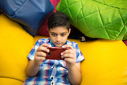 © Licensed to London News Pictures . 19/08/2015 . Oldham , UK . SAMI AKBAR (11) (correct) from Ashton (pictured playing games on a smart phone ), took and passed his GCSE maths at the age of ten . He achieved a B in two Higher Maths papers . Photo credit : Joel Goodman/LNP