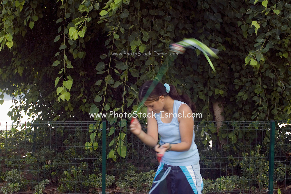A Young female teen, 13 years old, spinning Pois in a park