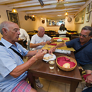 """VENICE, ITALY - JUNE 17: Three customers enjoy their cicchetti and wine at """"Ai Osti"""" on June 17, 2011 in Venice, Italy. The bacari are the local down to earth version of wine bars, they serve  """"cicheti"""" a sort of Tapas, traditionally washed down with a glass of wine, and Venetians stop to snack and socialize before and after meals."""