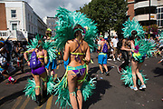 Parade dancers in feather costumes on Monday 28th August 2016 at Notting Hill Carnival in West London. A celebration of West Indian / Caribbean culture and Europes largest street party, festival and parade. Revellers come in their hundreds of thousands to have fun, dance, drink and let go in the brilliant atmosphere. It is led by members of the West Indian / Caribbean community, particularly the Trinidadian and Tobagonian British population, many of whom have lived in the area since the 1950s. The carnival has attracted up to 2 million people in the past and centres around a parade of floats, dancers and sound systems.