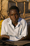 Abdel Karim Aboubakar, a Sudanese refugee at the Breidjing Refugee Camp in Eastern Chad. (Abdel Karim Aboubakar is featured in the book What I Eat: Around the World in 80 Diets.) The caloric value of his day's worth of food on a typical day in the month of November was 2300 kcals. He is 16 years of age; 5 feet 9.5 inches tall; and 110 pounds. Aboubakar escaped over the border from the Darfur region of Sudan into eastern Chad with his mother and siblings, just ahead of the Janjaweed militia that were burning villages of black Sudanese tribes. Like thousands of other refugees, they were accepted into the camp program administrated by the United Nations High Commission on Refugees. Their meals are markedly similar to those they ate in their home country; there's just less of it. They eat a grain porridge called aiysh, with a thin soup flavored with a dried vegetable or sometimes a small chunk of dried meat if Abdel Karim's mother has been able to work in a villager's field for a day or two. MODEL RELEASED. .