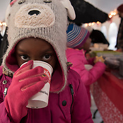 BRUNSWICK, Maine  11/24/18 -- Kaeja Dixon, 5, of Brunswick sips a mug of hot chocolate at the tree lighting event on Saturday.  <br /> Trevor Geiger, of Brunswick Downtown Association, said that the organization expected over 1500 guests at the event and that they counted participation by the number of cups of cocoa they passed out. He added that there were more than 20 volunteers helping out with the event and over 1500 cookies were on the table. Most were homemade, by volunteers. Photo by Roger S. Duncan for the Forecaster <br /> Photo by Roger S. Duncan for the Forecaster
