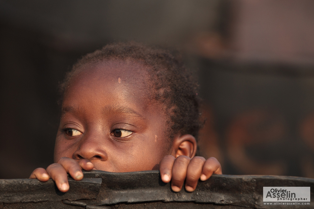 A girl peeks from behind a large barrel used to smoke fish in the West Point slum of Monrovia, Montserrado county, Liberia on Monday April 2, 2012.