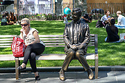 A woman seating next to Mr Bean's statue on a bench appears to be shy or keeping her distance from the Statue as she takes a rest in Leicester Square in London, on Wednesday, June 24, 2020. <br /> the UK officially recorded its warmest day of the year so far when the temperature reached 32.6C (90.7F) at London's Heathrow Airport at 2.46 pm. (Photo/ Vudi Xhymshiti)