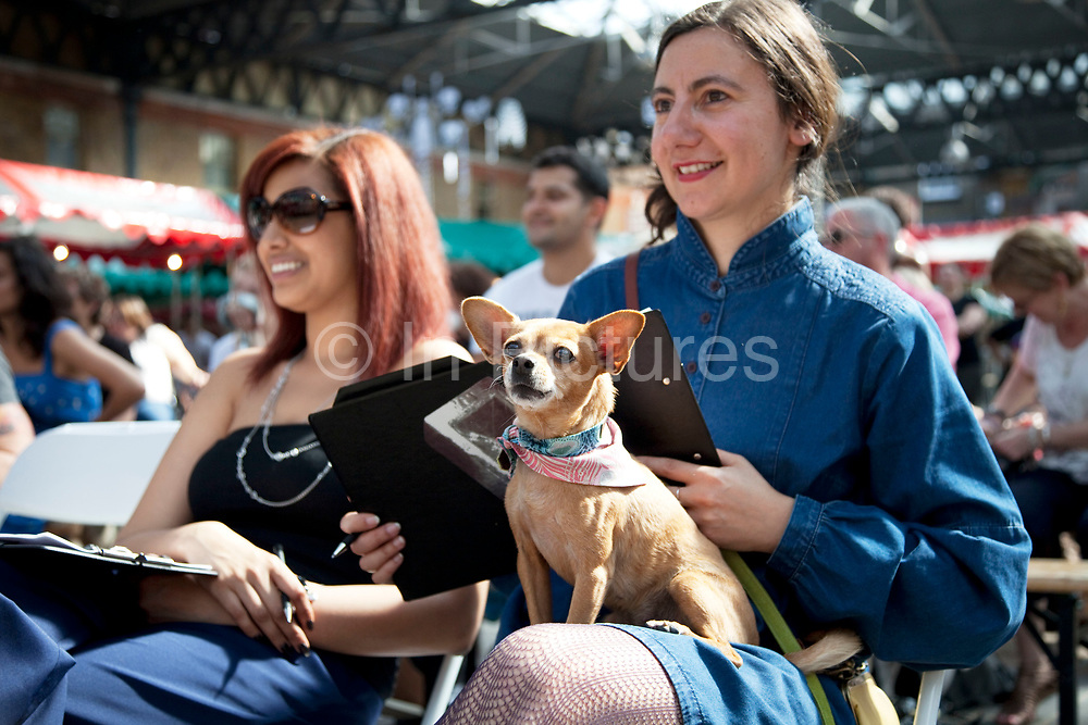 The judging panel at the Paw Pageant dog show at Spitalfields Market, London. Local people enter their dogs into the Shoreditch Unbound Festival Dog Show to win prizes and to show off their pets. Prizes and categories included: Dead Ringer, Dressed Up to the K-Nines, Fugliest Dog (meaning funny / ugly), Shoreditch Show Off, Paw-fection, Best in Ditch, Best Bitch in the Ditch.