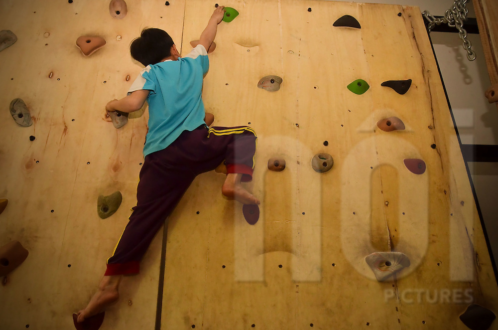 An orphan child at the Nguyen Viet Xuan in Hanoi is climbing on a climbing wall, indoor, as part of the Ta Ke project.