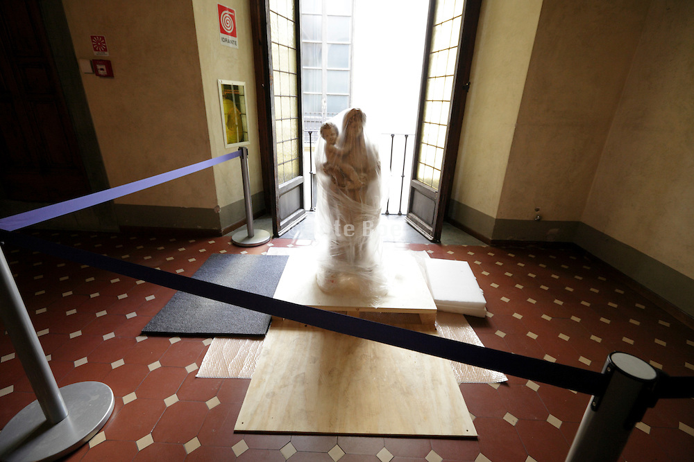old sculpture of Maria with baby Jesus covered with clear plastic, Palazzo Riccardi Florence Italy