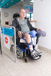 Male wheelchair user going through controlled wheelchair access gate at his local sports leisure centre,