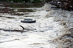 Torrential  rain causes the River Don to rise to within a few feet of overflowing its banks,  washing this car wheel alng in its torrent. The Don probably reached the highest level seen in the Meadowhall area of Sheffield since it burst it banks in 2007 flooding Meadowhall Shopping Centre and surrounding businesses..6 July 2012.Image © Paul David Drabble