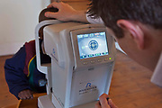 A male optician looks closely at the eye of an African school boy on a screen of the Rodenstock keratometer (opthalmometer) machine in a classroom in Zonnebloem School, Cape Town, South Africa.  The machine is an auto refractor and measures the curvature of the cornea.  The eye test is being provided by Mullers Opticians who volunteer their staff to visit schools and perform eye tests on all children in school grade 2.