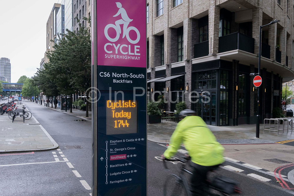 A cyclist rides past daily cycling statistics for the North-South CS6 Superhighway that allows commuters safe journeys south of Blackfriars Bridge, on 21st June 2021, in London, England.