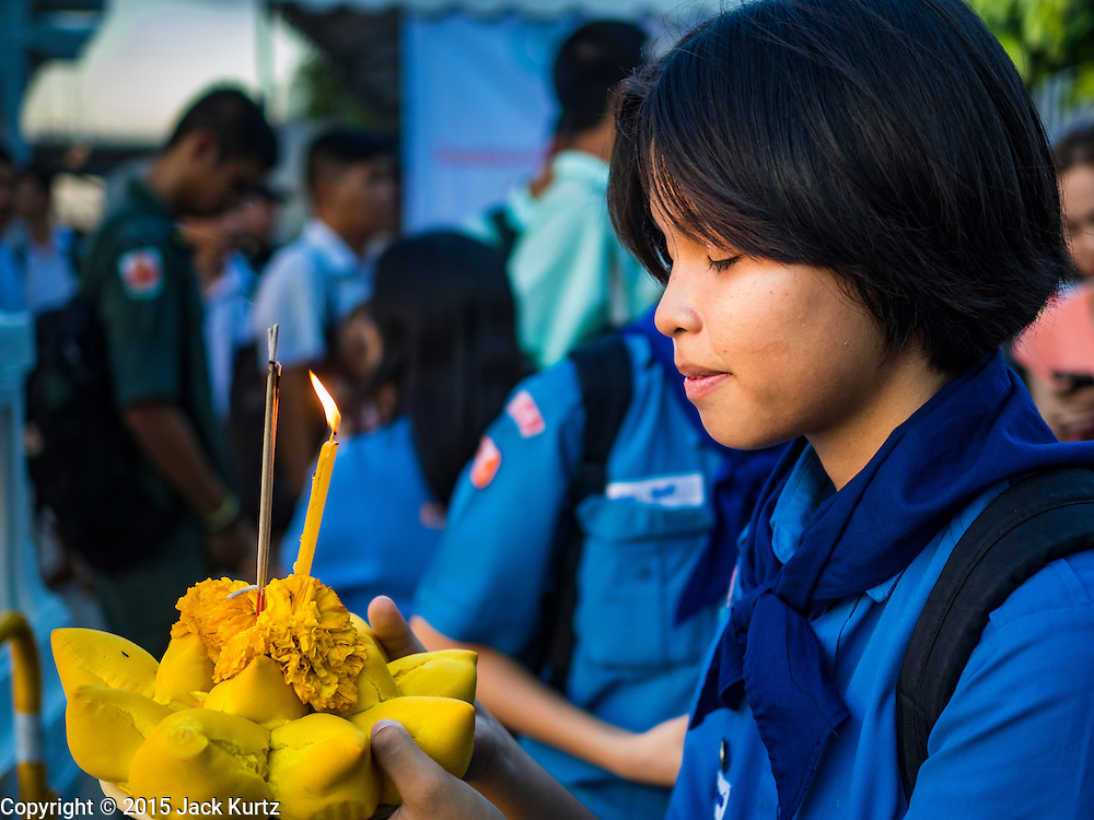 "25 NOVEMBER 2015 - BANGKOK, THAILAND:  A Thai ""Girl Guide"" (Girl Scouts in the US) prays before floating her krathong in the Chao Phraya River during Loy Krathong at Wat Yannawa in Bangkok. Loy Krathong takes place on the evening of the full moon of the 12th month in the traditional Thai lunar calendar. In the western calendar this usually falls in November. Loy means 'to float', while krathong refers to the usually lotus-shaped container which floats on the water. Traditional krathongs are made of the layers of the trunk of a banana tree or a spider lily plant. Now, many people use krathongs of baked bread which disintegrate in the water and feed the fish. A krathong is decorated with elaborately folded banana leaves, incense sticks, and a candle. A small coin is sometimes included as an offering to the river spirits. On the night of the full moon, Thais launch their krathong on a river, canal or a pond, making a wish as they do so.    PHOTO BY JACK KURTZ"