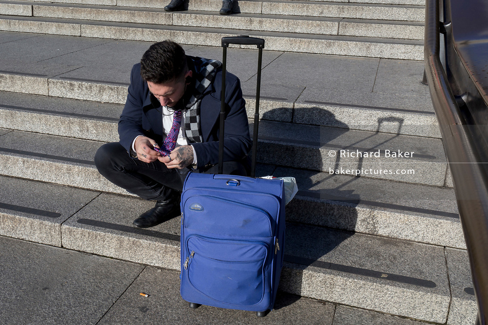 A tired traveller fiddles with his tie while resting with his baggage in winter sunshine on the steps in Trafalgar Square, on 22nd January 2019, in London England.