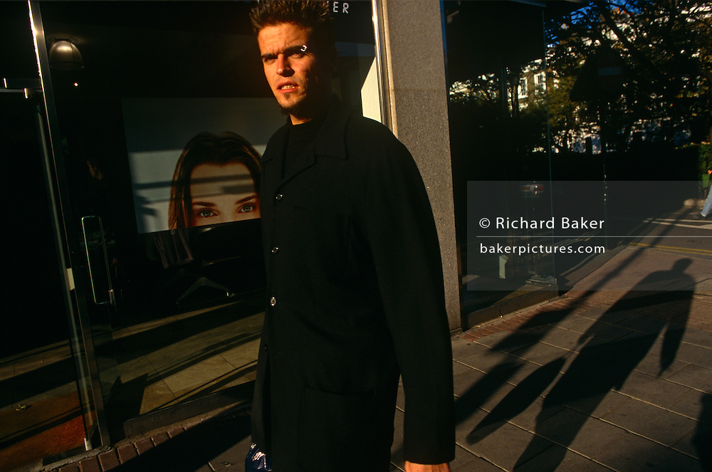 A young male shopper walks along the Kings Road in Chelsea, past a woman's clothing shop, with a female face in wondow.