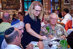 Glenda Werbel, left, dips the greens or Karpas in water, symbolizing spring.   Passover Seder with The Hebrew Congregation of St. Thomas led by Rabbi Mike Harvey at Lillienfeld House.   St. Thomas, USVI.  22 April 2016.  © Aisha-Zakiya Boyd