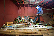 ****COPY HERE****  (https://www.dropbox.com/s/5mg81qiiuy22tre/adamson.rtf?dl=0)   © Licensed to London News Pictures. 02/12/2014. Liverpool , UK . Volunteer Graham Dean sorts through condemned pipes, all of which will need replacing or repairing. The only surviving steam powered tug tender, the Daniel Adamson, is being completely renovated by a team of volunteers in Liverpool. The vessel, which has had 90,000 man hours already spent on it, was bought for only one pound is the awaiting the decision of the Heritage Lottery Fund on an application of £3.6m to bring her back to her full glory.  . Photo credit : Stephen Simpson/LNP<br /> <br /> COPY HERE https://www.dropbox.com/s/5mg81qiiuy22tre/adamson.rtf?dl=0