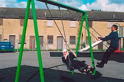 Children playing on swings; Bradford Yorkshire UK
