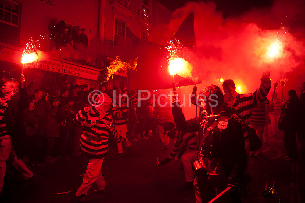 Lewes, UK. Monday 5th November 2012. Cliffe bonfire society members carry burning torches. Bonfire Night celebration in the town of Lewes, East Sussex, UK which form the largest and most famous Guy Fawkes Night festivities. Held on 5 November, the event not only marks the date of the uncovering of the Gunpowder Treason and Plot in 1605, but also commemorates the memory of the 17 Protestant martyrs from the town burnt at the stake for their faith during the Marian Persecutions of 1555–57. There are six bonfire societies putting on parades involving some 3,000 people.