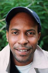 Portrait of young man wearing baseball cap smiling,