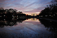 The Lincoln Memorial glows at sunset, with sweeping clouds painted in dramatic colors reflected in the pool below.