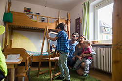Older brother is writing on a blackboard, parents and the little brother are watching, Munich, Germany
