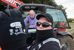 Aylesbury Vale, UK. 1st October, 2020. A National Eviction Team bailiff obstructs the photographer's camera as a farmer in a telehandler positioned on land not compulsorily purchased by HS2 Ltd asks for clarification as to why a fence is being erected across his field during the eviction of anti-HS2 activists from a wildlife protection camp in ancient woodland at Jones' Hill Wood. Around 40 environmental activists and local residents, some of whom living in makeshift tree houses, were present during the evictions at Jones' Hill Wood which had served as one of several protest camps set up along the route of the £106bn HS2 high-speed rail link in order to resist the controversial infrastructure project.
