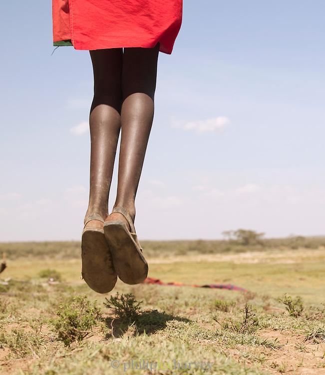 Maasai tribesman in traditional dance called Adumu, a jumping competition. Near Maasai Mara National Reserve, Kenya