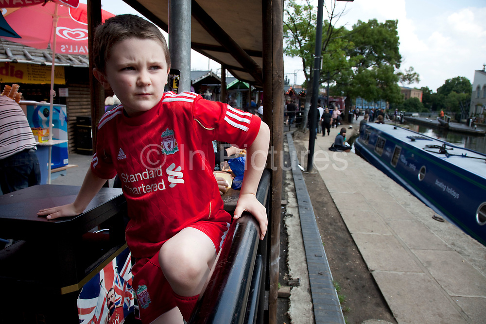 LONDON, ENGLAND, UK, JUNE 11TH 2011. Kiefer (8, wearing a red Liverpool Football Club kit) spending a day out together in Camden Town, North London. Playing after lunch. Louise (his mother) is on various benefits to help support her family income, and housing, although recent government changed to benefits may affect her family drastically, possibly meaning they may have to move out of London. Louise Ryan was born on the Wirral peninsula in 1970.  She moved to London with her family in 1980.  Having lived in both Manchester and Ireland, she now lives permanently in North London with her husband and two children. Through the years Louise has battled to recover from a serious motorcycle accident in 1992 and has recently been diagnosed with Bipolar Affective Disorder. (Photo by Mike Kemp/For The Washington Post)