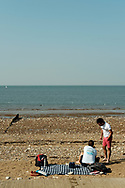 A man stands talking to a lady sitting on a beach matt, surrounded by belongings as they enjoy the summer sunshine. Taken on the last hot day of the Summer in Hunstanton Norfolk, the first summer in the UK during the COVID-19 pandemic.<br /> <br /> Photo by Jonathan J Fussell, COPYRIGHT 2020