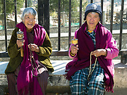 Two Bhutanese woman holding prayer wheels and rosary beads praying at the National Memorial Chorten in Thimphu, Western Bhutan. This large Tibetan-style chorten is one of the most visible religious structures in Thimphu and for many Bhutanese it is the focus of their daily worship. It was built in 1974 as a memorial to the third king, Jigme Dorji Wangchuck. Throughout the day people circumambulate the chorten, whirl the large red prayer wheels and pray at a small shrine inside the gate.