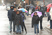 Onlookers await the passing of a Good Friday Via Crucis along W. Pratt Blvd. in Chicago's Rogers Park neighborhood. The religious portrayal recounts the biblical steps of Jesus Christ being condemned to death, followed by his crucifixion and entombment.