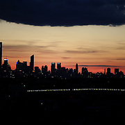 The sun sets behind the Manhattan skyline in New York City viewed from Flushing, Queens, as the seven train heads to Flushing. New York. USA. Photo Tim Clayton